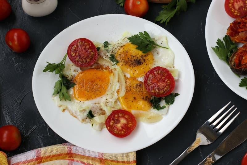 Os ovos mexidos com tomates de cereja são ficados situados em uma placa branca em um fundo escuro, a foto lá cozeram beringelas,  imagem de stock