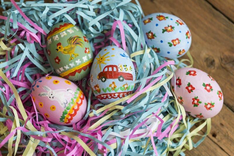 Os ovos pintados encontram-se em uma cesta, fundo de madeira, easter foto de stock royalty free