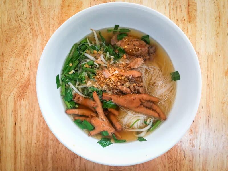 Os pés cozidos da galinha da sopa de macarronete da aletria do arroz rolam no fundo de madeira da tabela foto de stock