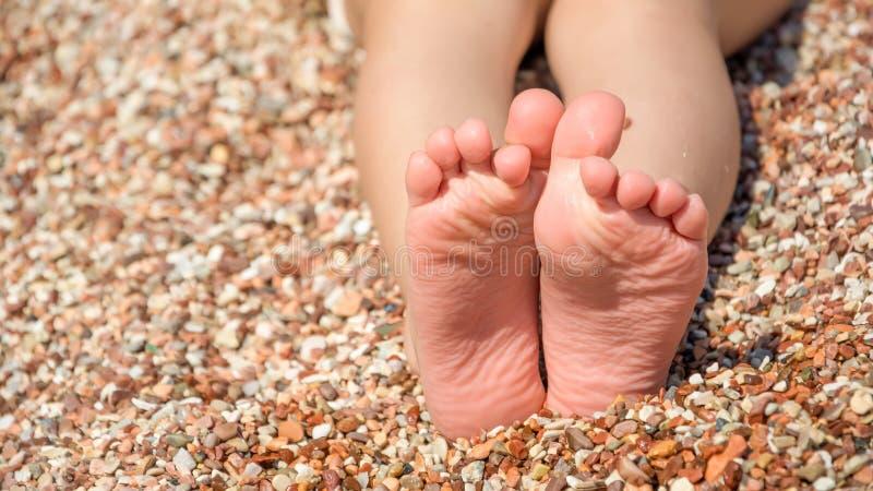 Os pés da criança na praia dos seixos fotografia de stock royalty free