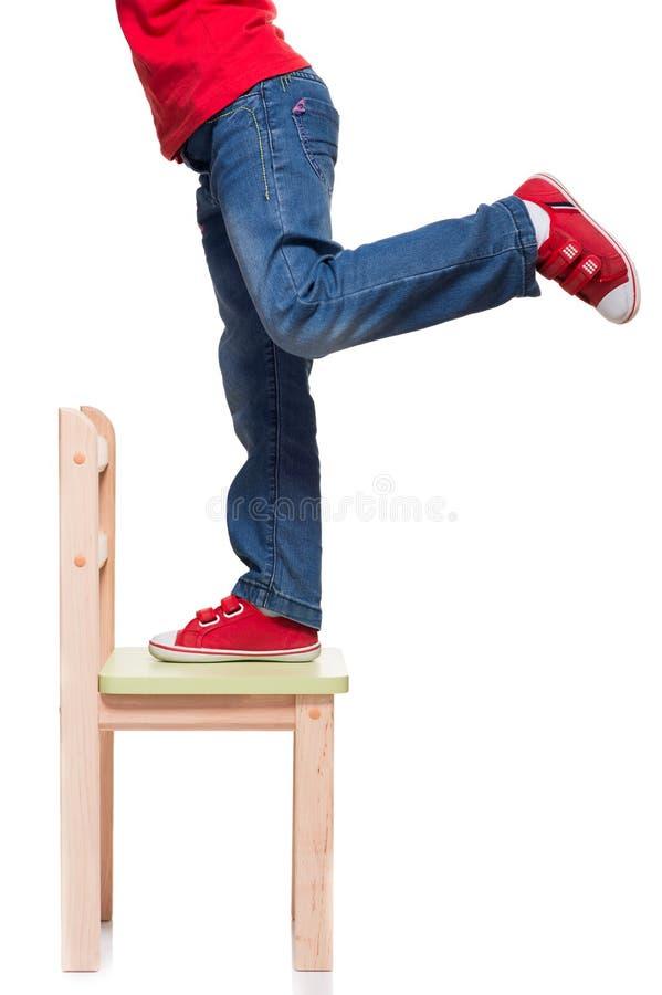 Os pés da criança que estão na cadeira pequena foto de stock