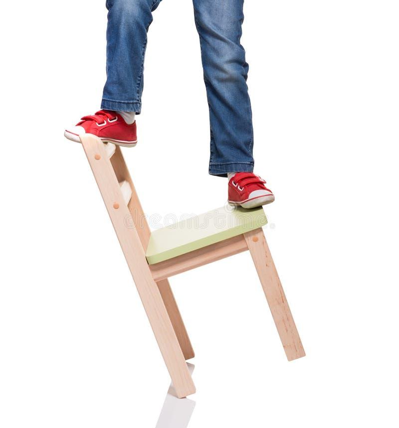 Os pés da criança que estão na cadeira pequena imagens de stock