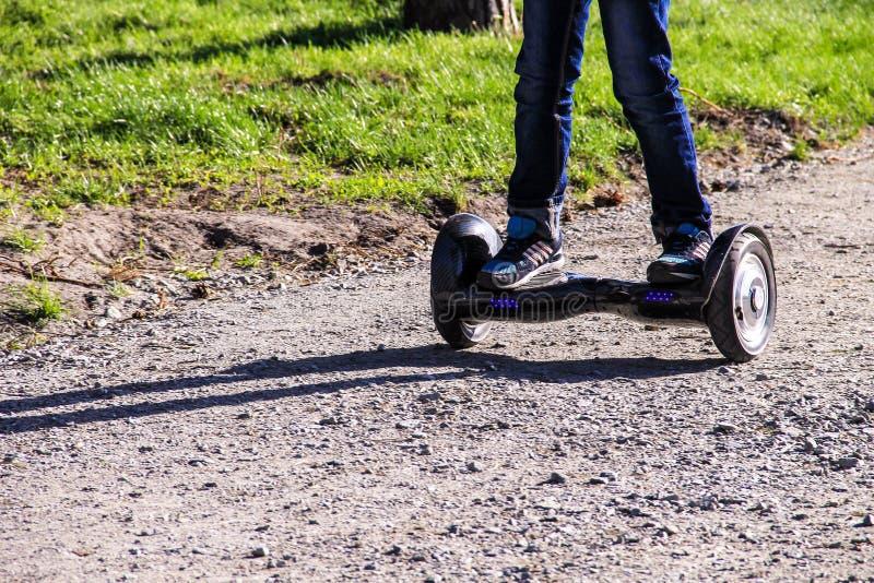 Os pés da equitação do menino em auto-equilibrar o mini hoverboard na cidade estacionam imagem de stock