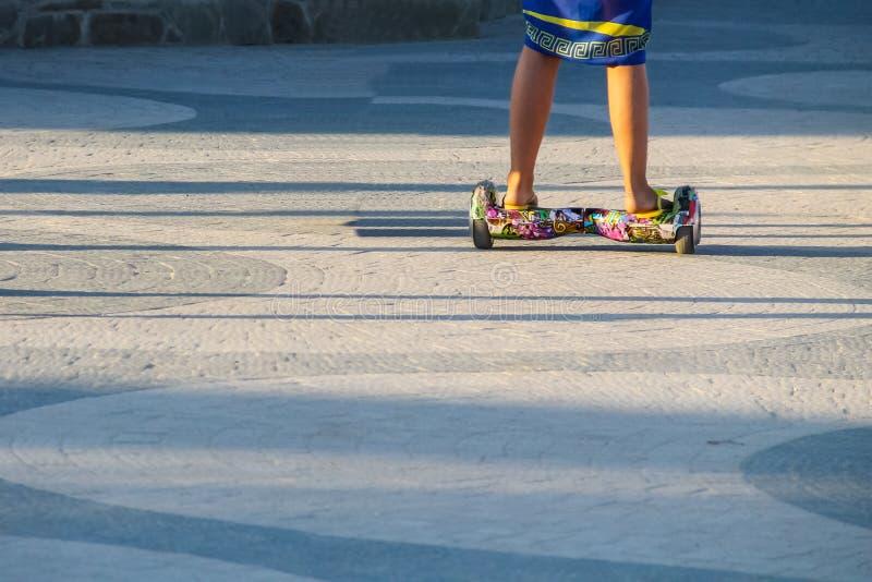 Os pés da equitação da menina em auto-equilibrar o mini hoverboard na cidade estacionam imagens de stock royalty free