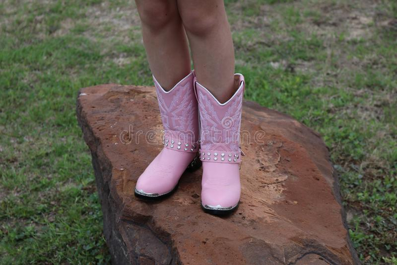 Os pés da menina em botas cor-de-rosa fotos de stock royalty free