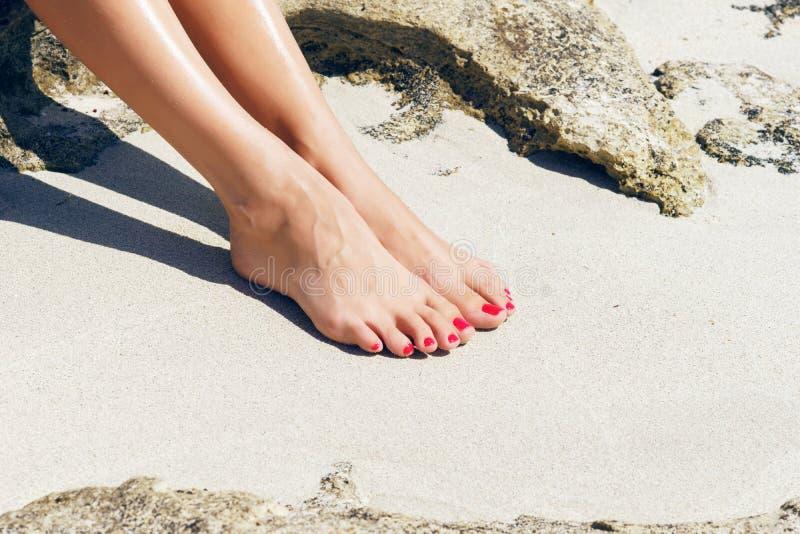 Os pés da mulher bonita com pedicure vermelho fotografia de stock royalty free