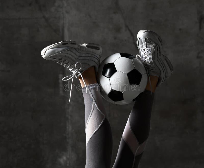Os pés da mulher com a bola de futebol no muro de cimento loft imagem de stock royalty free