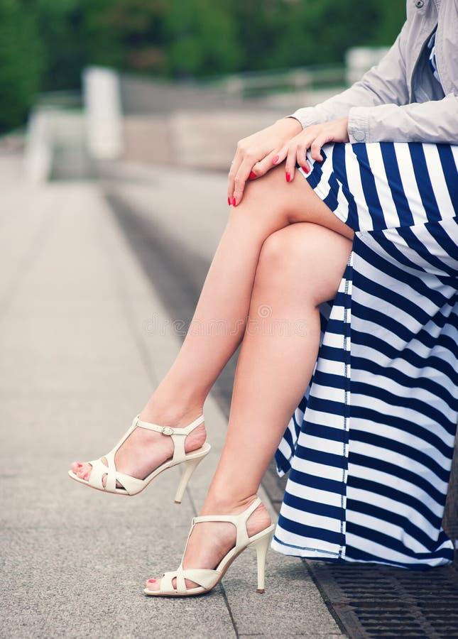 Os pés da mulher com saltos altos vestiram o vestido por muito tempo listrado foto de stock