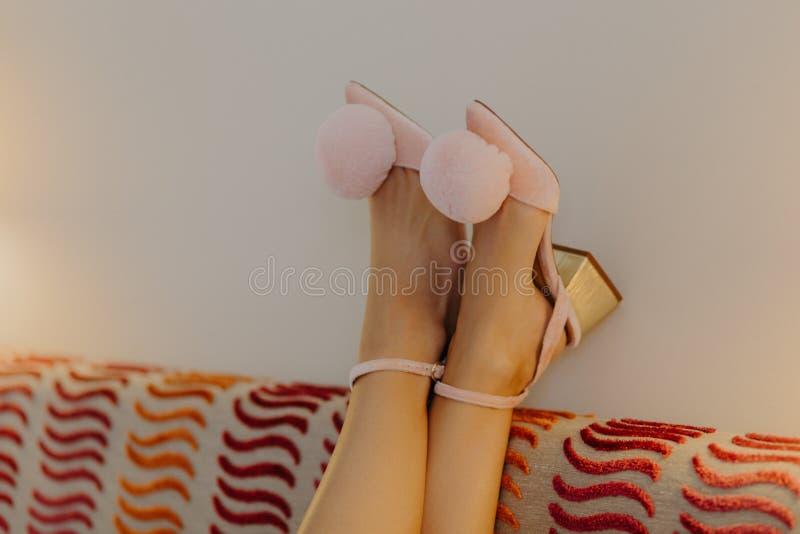 Os pés da mulher delgada macia em sapatas cor-de-rosa elegantes no lado do sofá Mulher cansado após o dia de trabalho duro, foco  foto de stock