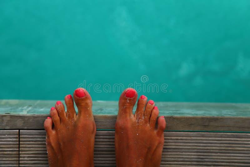 Os pés da mulher estão na ponte de madeira sobre o mar Feriado das férias que aprecia o sol no conceito ensolarado do dia de verã foto de stock