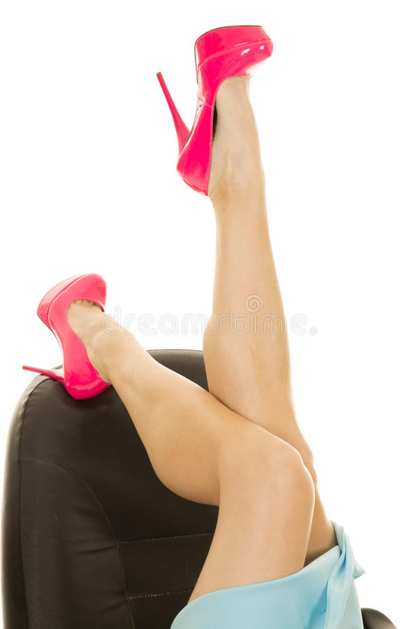 Os pés da mulher na configuração cor-de-rosa dos saltos no escritório presidem a saia azul uma acima imagem de stock royalty free