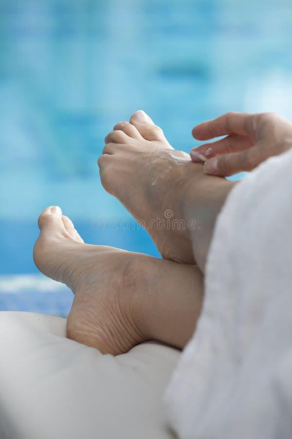 Os pés da mulher na piscina fotos de stock royalty free