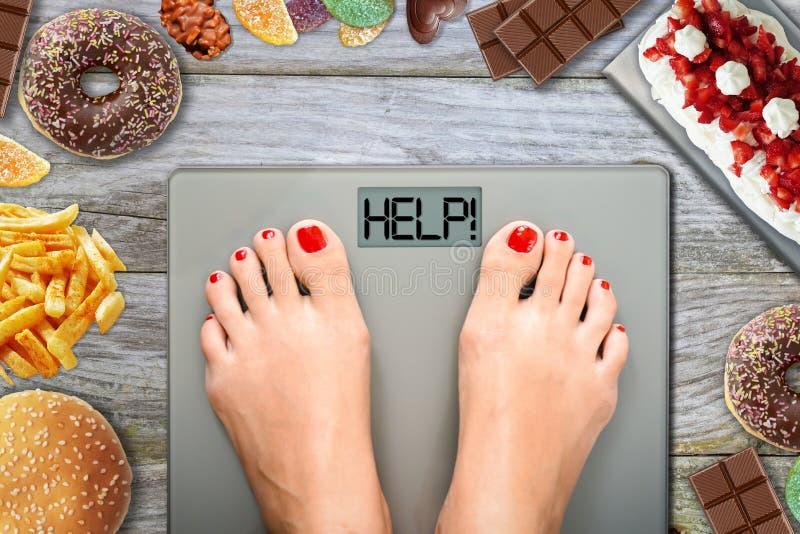 Os pés da mulher na ponderação escalam pedir a ajuda evitar a tentação comer o alimento insalubre imagens de stock