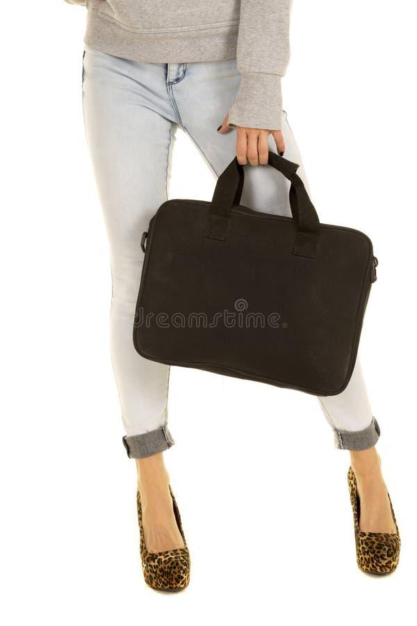 Os pés da mulher na sarja de Nimes e nos saltos com saco preto fronteiam foto de stock royalty free
