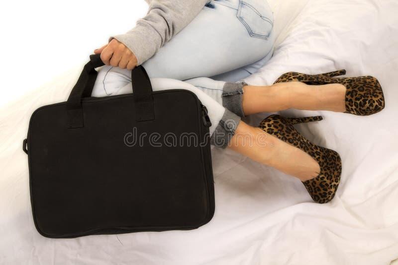 Os pés da mulher na sarja de Nimes e nos saltos com saco preto sentam-se imagem de stock