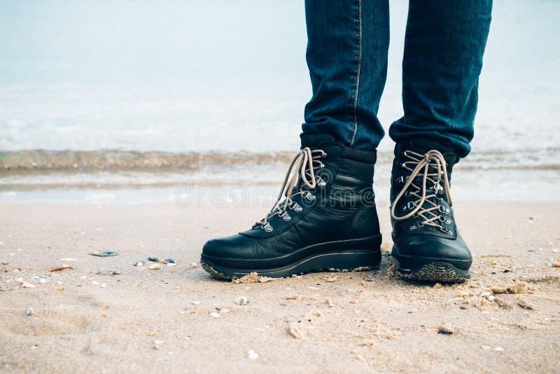 Os pés da mulher nas botas no Sandy Beach fotografia de stock royalty free