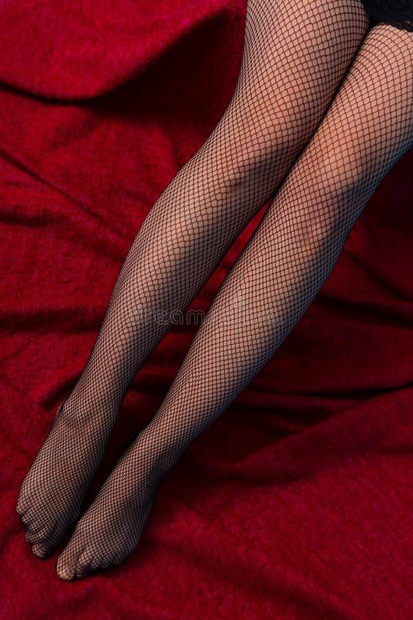 Os pés da mulher nas redes de pesca foto de stock royalty free