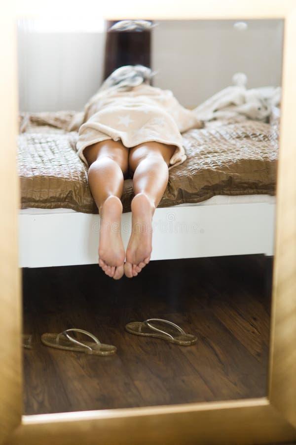 Os pés da mulher no espelho quadro no quadro dourado fotografia de stock