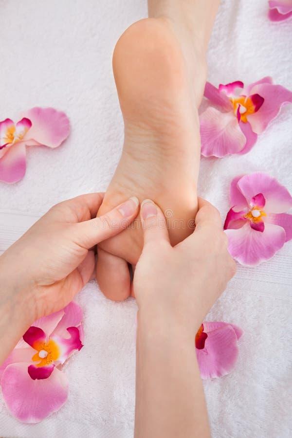 Os pés da mulher que recebem a massagem do pé imagens de stock royalty free