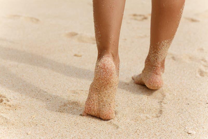 Os pés das meninas que correm na areia branca encalham foto de stock royalty free