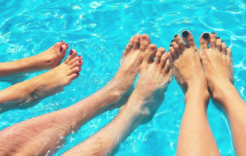 Os pés das mulheres e dos homens na associação Férias no verão no tempo claro imagens de stock royalty free