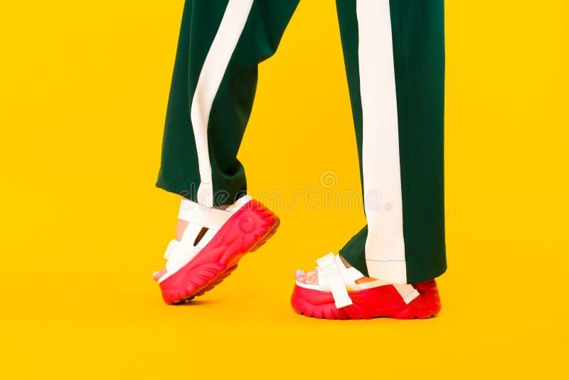 Os pés das mulheres em sandálias do esporte com solas vermelhas e em calças verdes com listras imagens de stock
