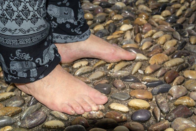 Os pés das mulheres estão nas pedras lisas da fuga de endurecimento para a massagem do pé foto de stock