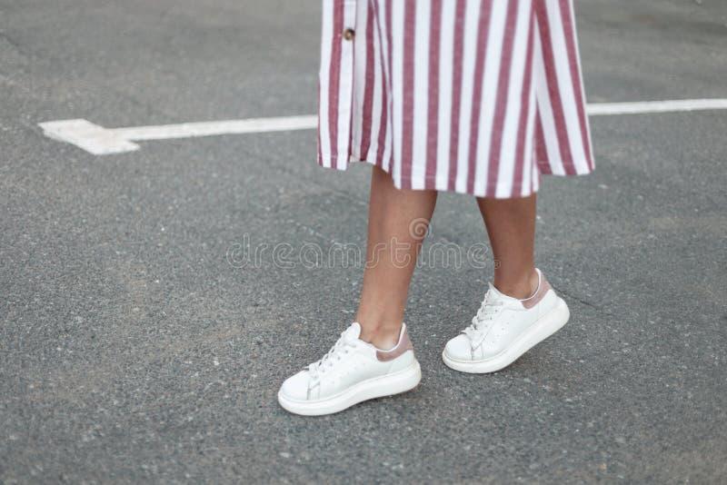Os pés das mulheres no vestido listrado cor-de-rosa à moda no as sapatilhas de couro na moda brancas estão na estrada na cidade foto de stock royalty free