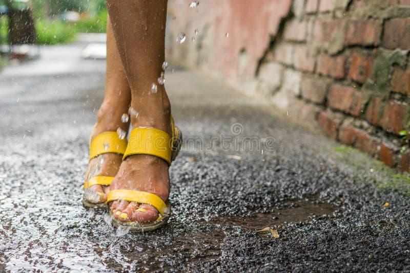 Os pés das mulheres sob as gotas da chuva fotografia de stock royalty free