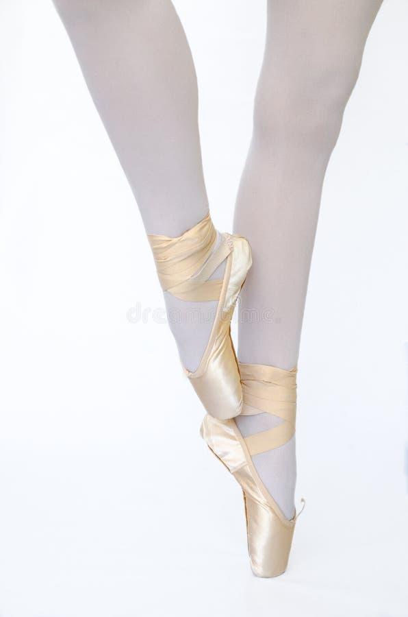 Os pés de Balleina no bacground branco do pointe de rosa fotos de stock