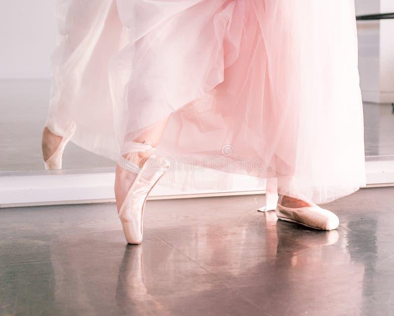 Os pés de Ballerine em sapatas do pointe e no tutu pairoso cor-de-rosa contornam o reflecte fotos de stock royalty free