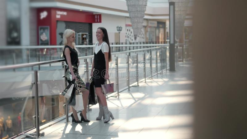 Os pés de duas meninas na forma vestem o passeio com os sacos no shopping, fim acima das meninas nos saltos altos imagens de stock