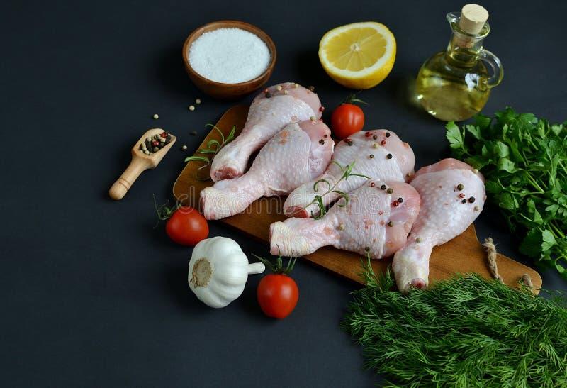 Os pés de galinha crus com ervas e as especiarias verdes salpicam foto de stock