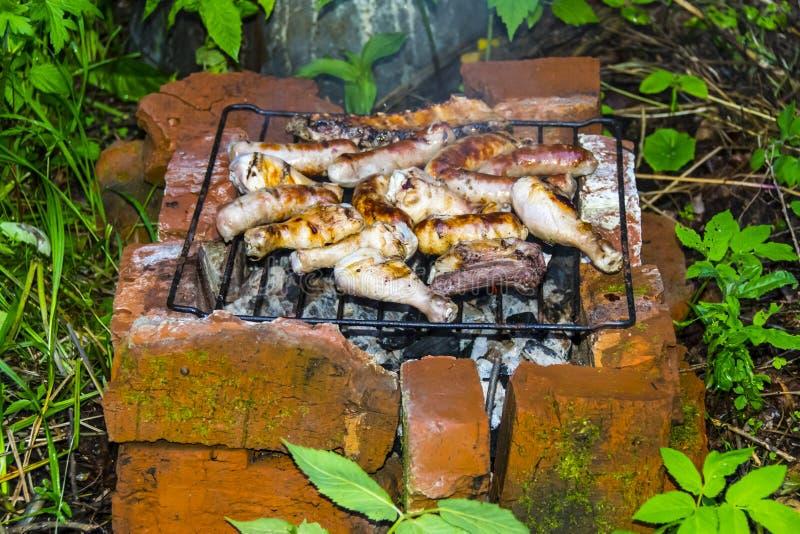 Os pés de galinha dos reforços de carne de porco da salsicha na grade assam o forno do tijolo foto de stock