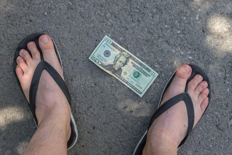 Os pés de um adolescente perto da cédula que encontra-se no asfalto imagens de stock royalty free