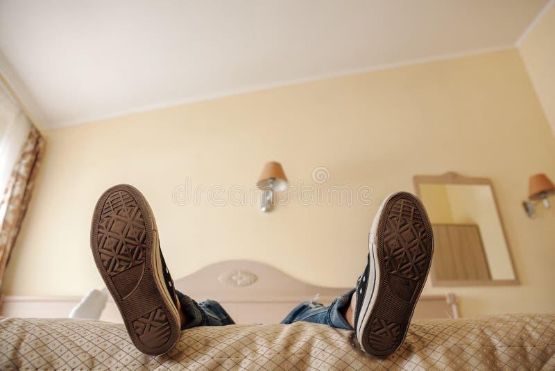 Os pés de uma menina que seja cansada e de encontro na cama Sapata das solas da foto imagens de stock