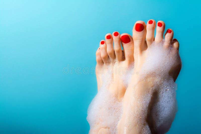 Os pés de uma moça com os pregos vermelhos com gotas do creme esfregam e dos feijões de café ao redor em um azul imagem de stock