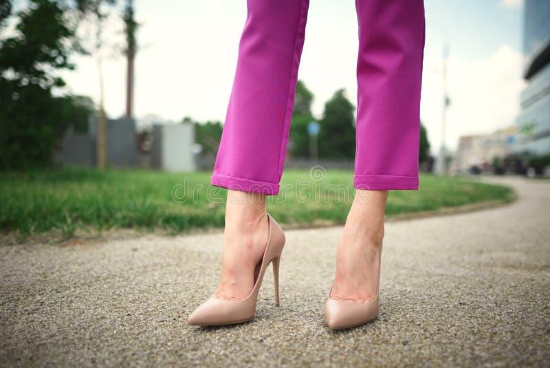 os pés de uma moça nos saltos estão na rua imagens de stock