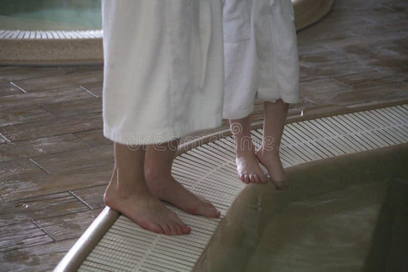 Os pés de uma mulher e de uma criança perto da associação em uns termas centram-se foto de stock