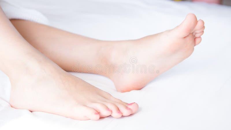 Os pés desencapados da mulher na cama na sala clara Pé fêmea bonito e elegante Os termas, esfregam e o conceito do cuidado de pé imagens de stock royalty free