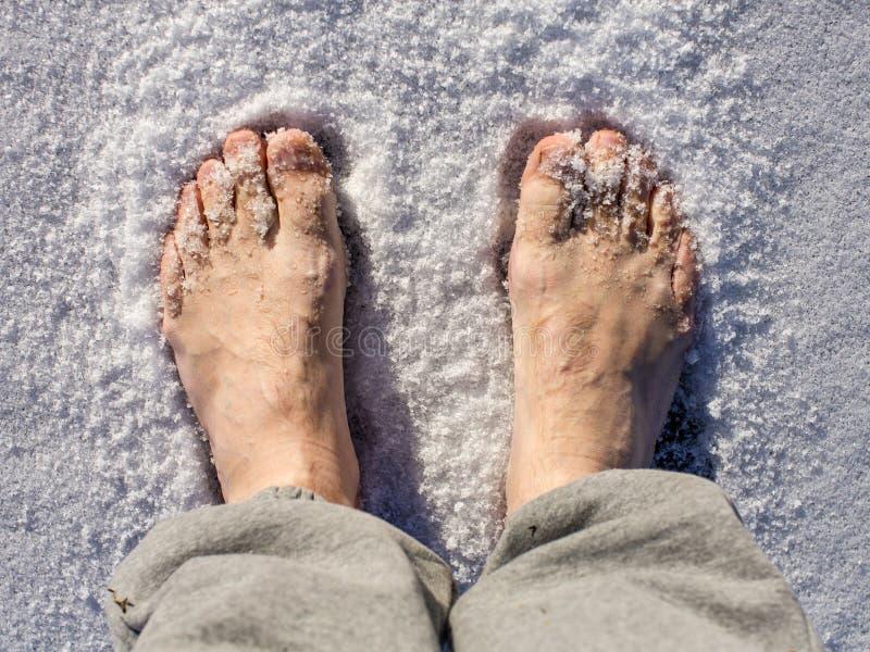 Os pés desencapados dos homens na neve em um dia ensolarado foto de stock royalty free