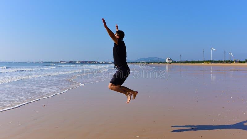 Os pés desencapados equipam o salto na praia com ondas imagem de stock