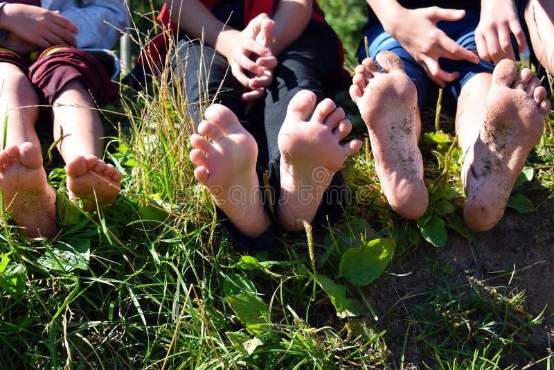 Os pés despidos das crianças dos pés fora As crianças sentam-se em uma grama e nos pés da mostra fotografia de stock