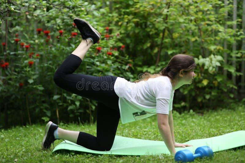 Os pés do elevador da menina do adolescente fazem exercícios para o stomack liso com peso imagens de stock