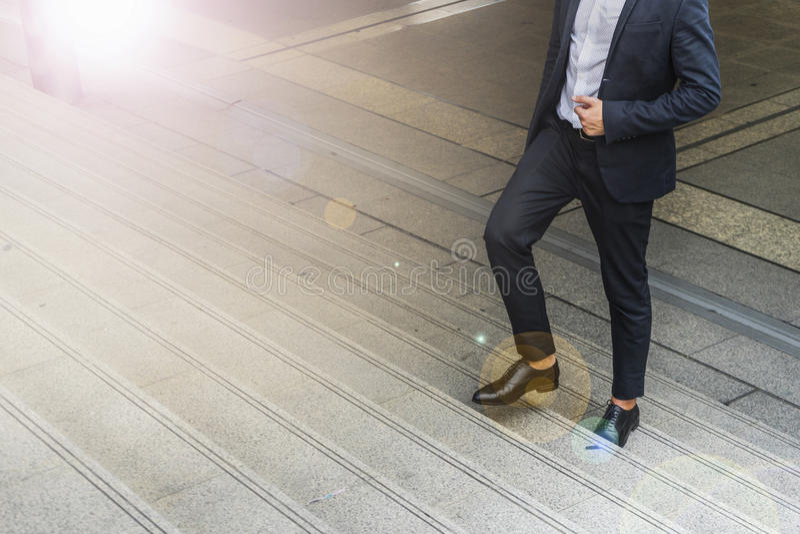 Os pés do homem de negócios vestem o terno preto que anda intensificando a escada na cidade moderna, o negócio cresce acima e con foto de stock
