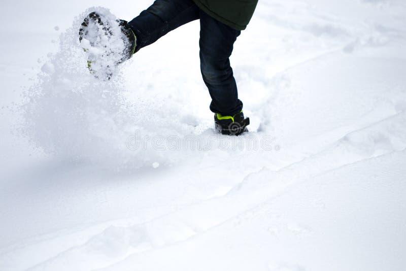 Os pés do menino andam através da neve A neve voa de debaixo de seu f imagens de stock