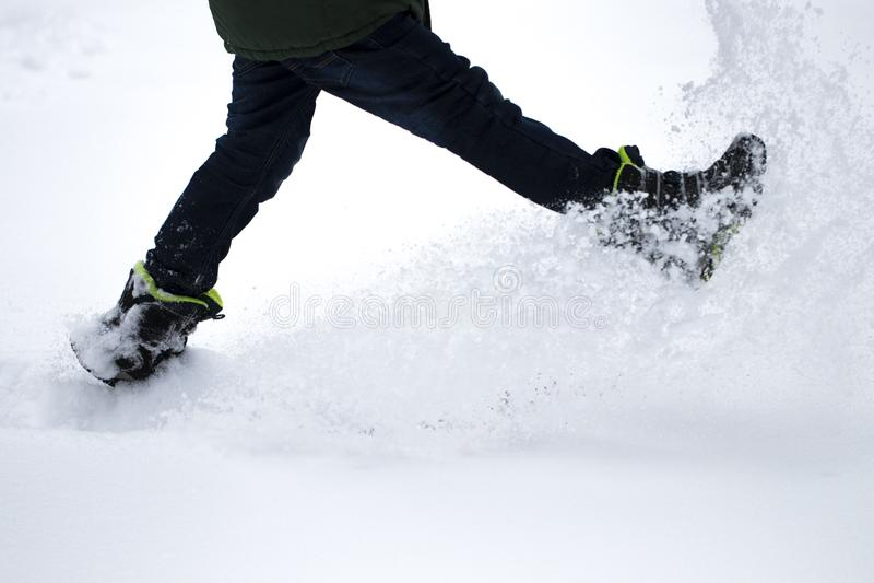 Os pés do menino andam através da neve A neve voa de debaixo de seu f fotos de stock royalty free