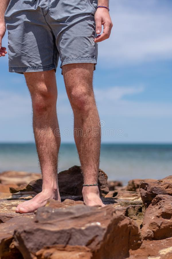 Os pés do menino na praia imagem de stock