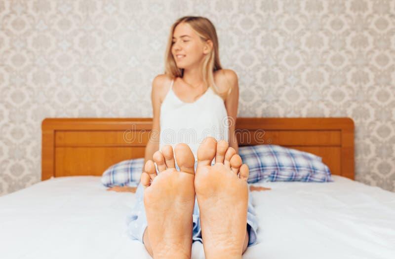 Os pés do ` s da menina na cobertura branca na cama, menina acordaram na cama no amanhecer imagem de stock