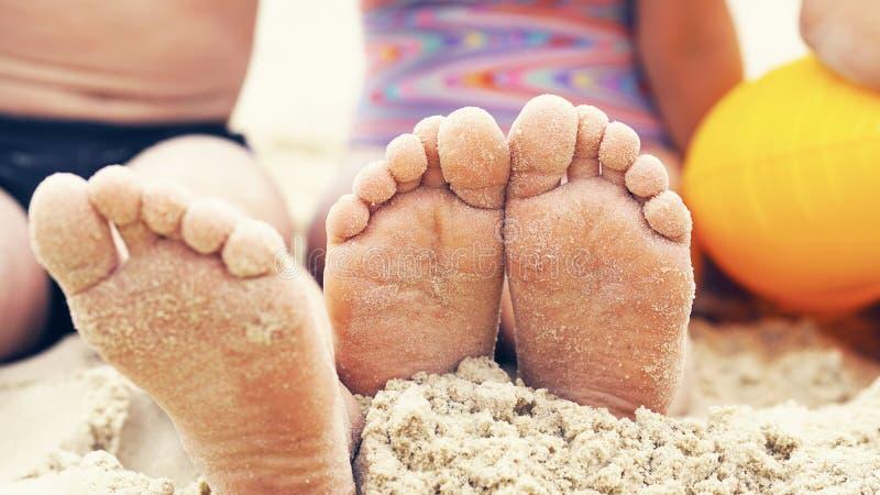 Os pés do ` s das crianças fecham uplying na areia Feriado feliz na costa de mar imagem de stock royalty free